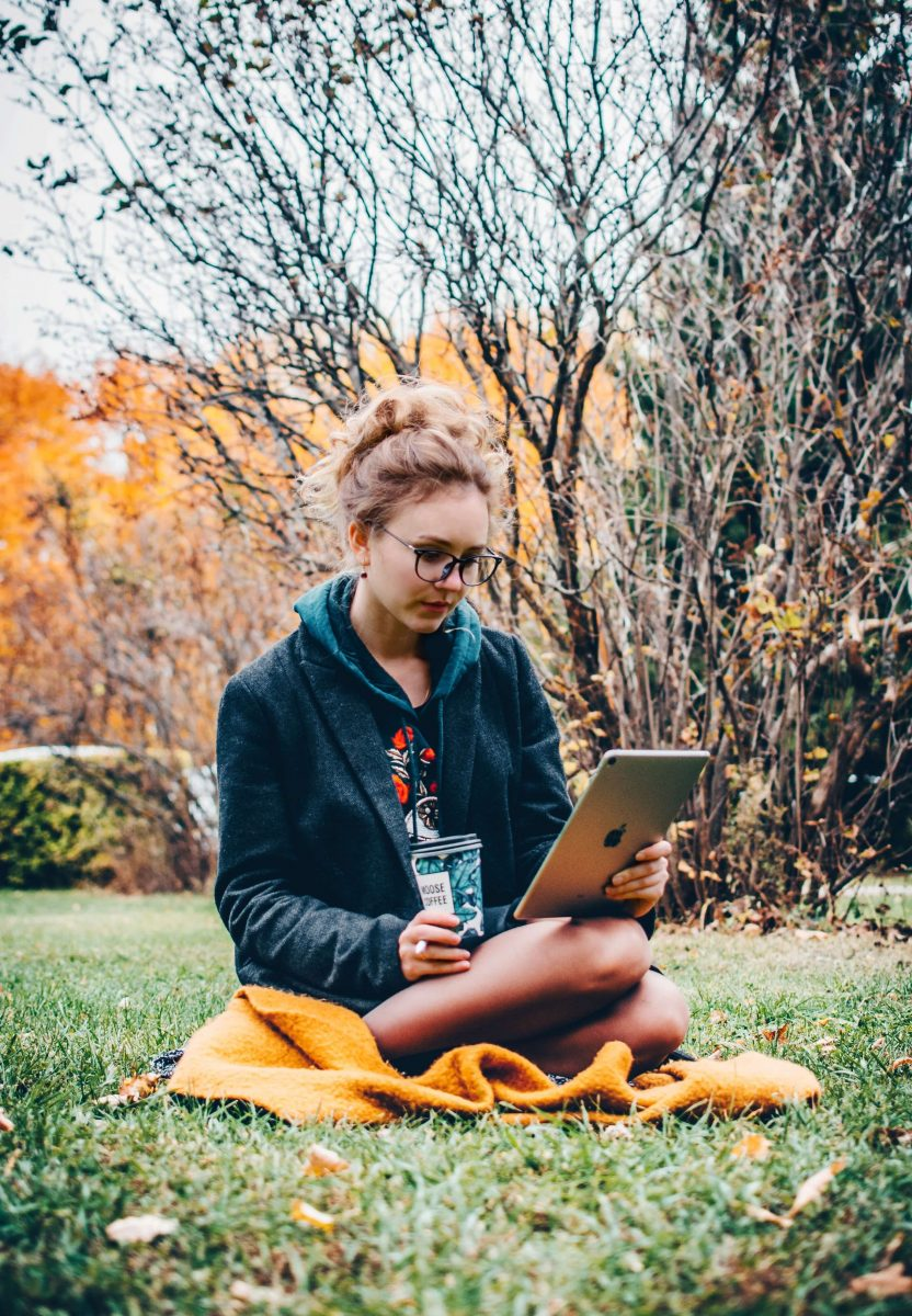 meisje op haar iPad in een park met een gele deken